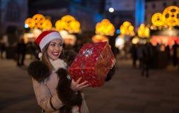 拿着圣诞节礼物的美丽的妇女在晚上 库存图片
