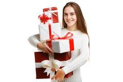 拿着圣诞节礼物的逗人喜爱的微笑的小女孩被隔绝在白色背景 节假日概念 库存照片