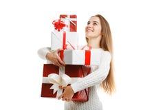 拿着圣诞节礼物的逗人喜爱的微笑的小女孩被隔绝在白色背景 节假日概念 免版税库存图片
