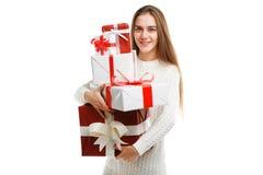 拿着圣诞节礼物的逗人喜爱的微笑的小女孩被隔绝在白色背景 节假日概念 免版税图库摄影