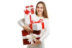 拿着圣诞节礼物的逗人喜爱的微笑的小女孩被隔绝在白色背景 节假日概念 免版税库存照片