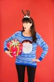 拿着圣诞节礼物的鹿角冠状头饰的妇女 免版税库存照片