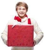 拿着圣诞节礼物的年轻滑稽的人 免版税库存照片