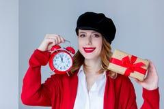 拿着圣诞节礼物盒和红色减速火箭的警报cloc的帽子的妇女 库存图片