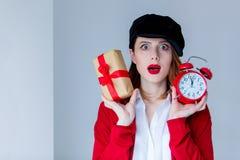 拿着圣诞节礼物盒和红色减速火箭的警报cloc的帽子的妇女 免版税库存照片