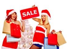 拿着圣诞节礼物盒的圣诞老人帽子的女孩 免版税库存图片