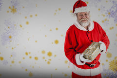 拿着圣诞节礼物盒的圣诞老人画象的综合图象 免版税库存照片