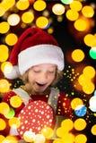 拿着圣诞节礼物盒的惊奇的孩子 库存照片