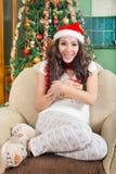 拿着圣诞节礼物箱子的愉快的少妇戴圣诞老人帽子 库存照片