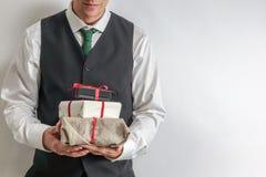 拿着圣诞节礼物/礼物箱子的衣服背心的人 免版税库存照片