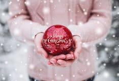 拿着圣诞节红色球的女性手 冷淡的冬日在多雪的森林圣诞快乐和新年快乐里 免版税图库摄影
