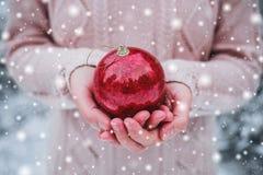 拿着圣诞节红色球的女性手 冷淡的冬日在多雪的森林里 免版税库存照片