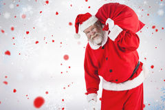 拿着圣诞节袋子的圣诞老人画象的综合图象 库存照片