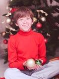 拿着圣诞节装饰的愉快的孩子在屋子里 免版税库存照片