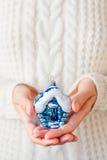 拿着圣诞节装饰-房子的被编织的毛线衣的妇女 免版税库存照片
