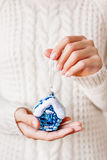 拿着圣诞节装饰-蓝色房子的毛线衣的妇女 免版税库存照片