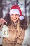 拿着圣诞节la的圣诞老人帽子的圣诞节打过工–愉快的妇女 免版税库存图片
