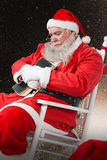 拿着圣经的圣诞老人的综合图象,当放松在椅子时 免版税库存图片