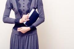 拿着圣经的灰色葡萄酒礼服的年轻美丽的妇女 免版税库存照片