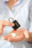 拿着在一个微型房子的屋顶的女商人一把暗号锁,象征住家安全或保险的概念 免版税图库摄影