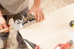 拿着在一个木板的木工一套夹具 免版税图库摄影