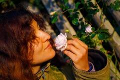 拿着在一个柔和的姿态的自然女孩一朵玫瑰花 库存图片