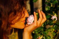 拿着在一个柔和的姿态的自然女孩一朵玫瑰花 免版税图库摄影