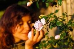 拿着在一个柔和的姿态的自然女孩一朵玫瑰花 免版税库存图片