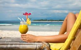 拿着在一个热带海滩的一个鸡尾酒 库存照片