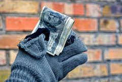 拿着在一副被撕毁的手套的无家可归的人金钱反对砖墙背景 库存图片