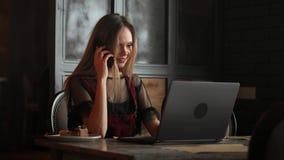 拿着在一张桌上的妇女手白色手机与一台膝上型计算机在办公室 股票录像