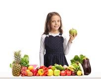 拿着在一张桌后的女孩一个苹果用水果和蔬菜 库存照片