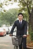 拿着在一条城市街道上的年轻,微笑的商人一辆自行车在北京,中国 免版税库存图片