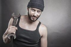 拿着在一织地不很细灰色backgro的英俊的粗砺的人一把板钳 免版税图库摄影