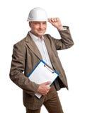 拿着在一件白色盔甲的土木工程师一个文件夹 免版税库存照片