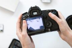 拿着在书桌的手一台照相机 免版税图库摄影