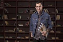 拿着在书橱前面的年轻愉快的人学生书 免版税库存照片