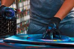 拿着在五颜六色的墙壁前面的人的手一个街道画喷壶 库存图片