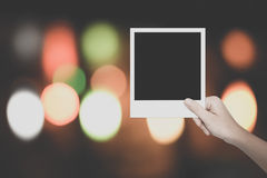 拿着在五颜六色的bokeh bac的女性的手一个空白的照片框架 免版税库存照片
