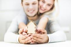 拿着在他们的被伸出的手上的可爱的年轻夫妇一种房子布局 买一栋新的公寓的概念 库存照片