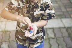 拿着在他手和使用上的亚裔男孩小企鹅玩具 免版税库存照片