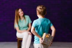 拿着在他的后的七岁的男孩一个礼物盒,坐在背景中的年轻女人 日母亲s 免版税库存照片