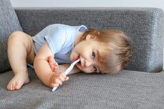 拿着在他的嘴的牙刷和清洗他的第一颗牙的逗人喜爱的矮小的微笑的男婴在沙发看的滑稽的姿势 免版税图库摄影