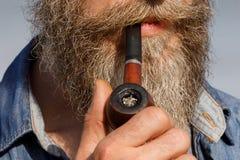 拿着在他的嘴,特写镜头的有胡子的人一只烟斗 库存图片