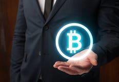 拿着在他的手上的商人bitcoin真正标志 库存图片