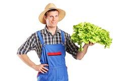 拿着在他的现有量的一位微笑的农夫一个莴苣 免版税库存照片