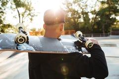 拿着在他的肩膀的年轻溜冰板者人滑板 免版税库存照片