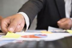 拿着在会议的年轻成功的人稠粘的便条纸在mod 免版税图库摄影