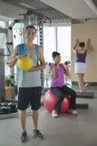 拿着在健身房的成熟人球,行使在背景的人们 免版税库存图片