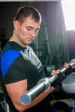 拿着在健身房的30岁的人杠铃 图库摄影